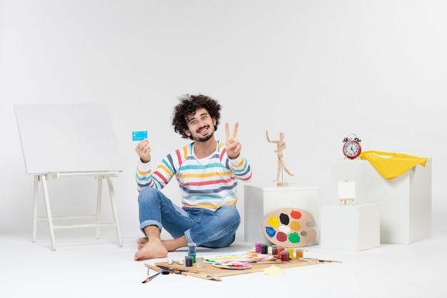 Vue de face du jeune homme tenant une carte bancaire sur un mur blanc