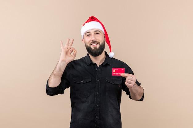 Vue de face du jeune homme tenant une carte bancaire rouge souriant sur le mur rose