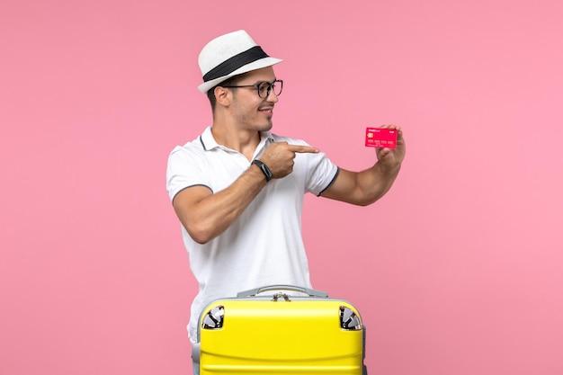 Vue de face du jeune homme tenant une carte bancaire rouge en vacances d'été sur le mur rose