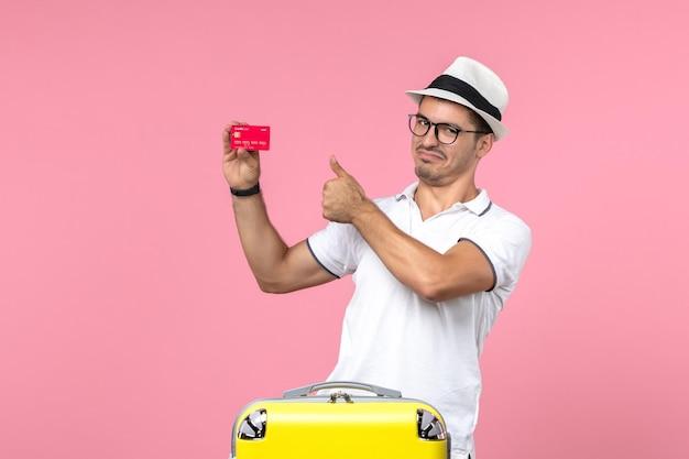 Vue de face du jeune homme tenant une carte bancaire rouge en vacances sur le mur rose