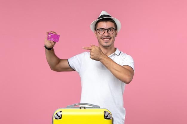 Vue de face du jeune homme tenant une carte bancaire en vacances d'été sur un mur rose clair