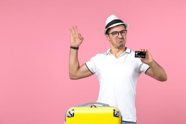 Vue de face du jeune homme tenant une carte bancaire en vacances d'été sur le mur rose