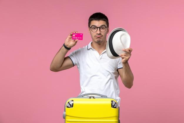 Vue de face du jeune homme tenant une carte bancaire en vacances sur le mur rose
