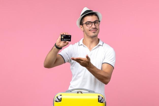 Vue de face du jeune homme tenant émotionnellement une carte bancaire noire sur un mur rose clair