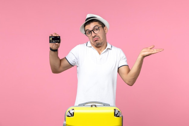 Vue de face du jeune homme tenant émotionnellement une carte bancaire noire sur le mur rose