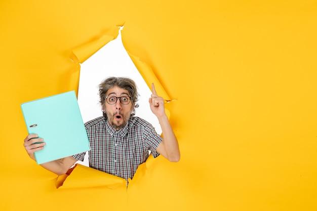 Vue de face du jeune homme tenant un fichier vert sur un mur jaune