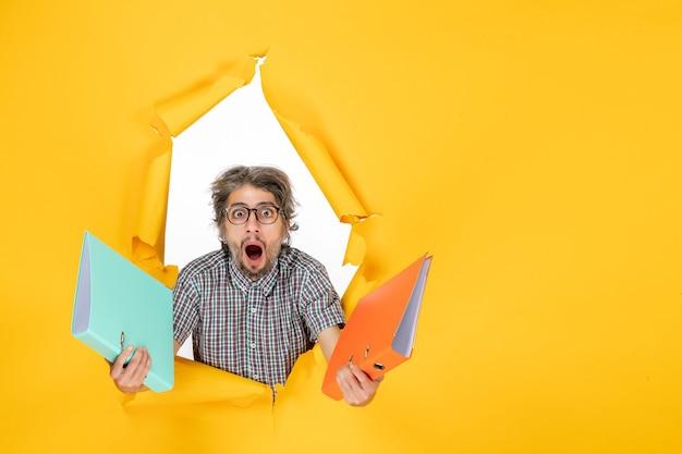 Vue de face du jeune homme tenant des fichiers sur un mur jaune