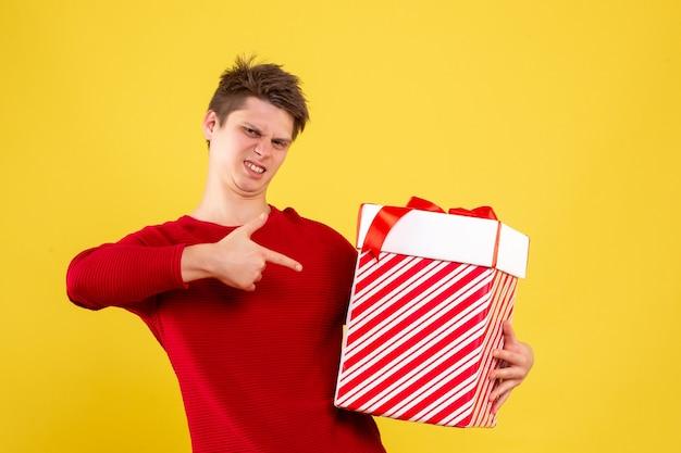 Vue de face du jeune homme tenant grand cadeau de noël sur mur jaune
