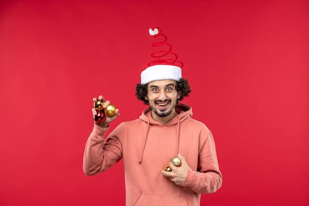 Vue de face du jeune homme tenant des jouets d'arbre de noël sur mur rouge