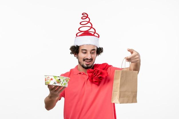 Vue de face du jeune homme tenant de la nourriture de livraison sur un mur blanc