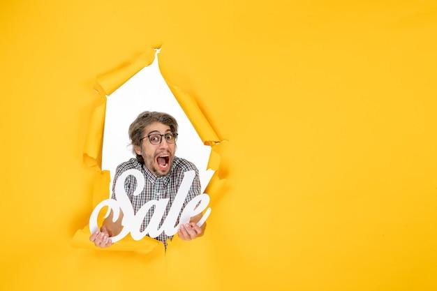 Vue de face du jeune homme tenant une vente par écrit sur un mur jaune