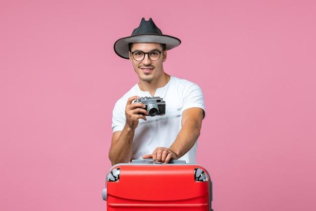 Vue de face du jeune homme en vacances d'été prenant des photos avec appareil photo sur le mur rose