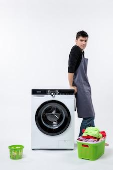 Vue de face du jeune homme avec des vêtements sales et une laveuse sur un mur blanc