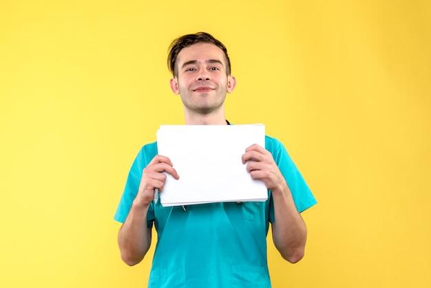 Vue de face du jeune médecin de sexe masculin avec des documents sur le mur jaune