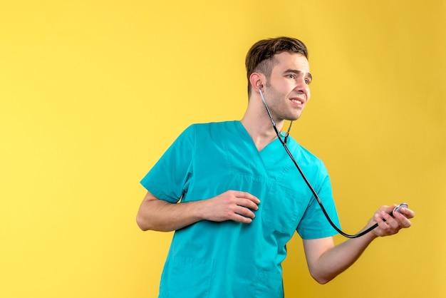 Vue de face du jeune médecin de sexe masculin avec stéthoscope sur mur jaune