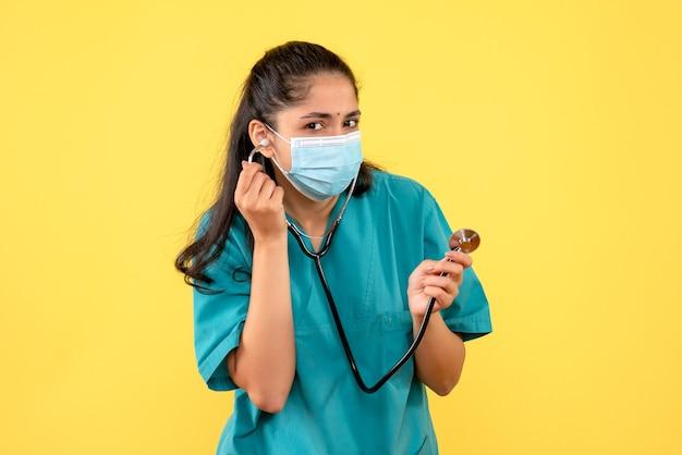 Vue de face du jeune médecin en uniforme à l'aide d'un stéthoscope debout sur un mur jaune