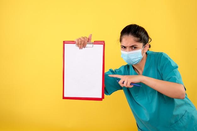 Vue de face du jeune médecin en uniforme pointant sur le presse-papiers sur le mur jaune