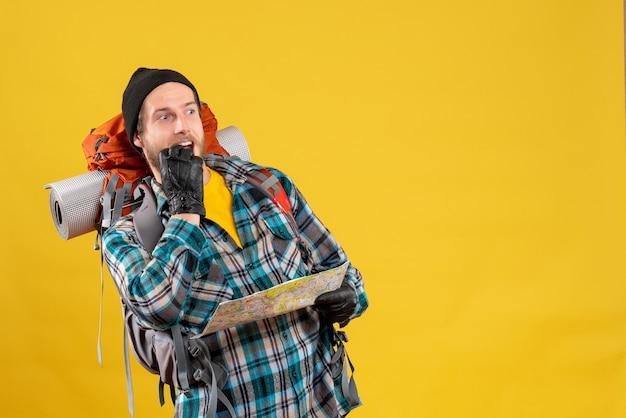 Vue de face du jeune routard curieux avec chapeau noir tenant la carte en regardant quelque chose