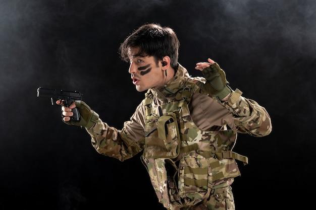 Vue de face du jeune soldat avec arme en camouflage sur mur noir