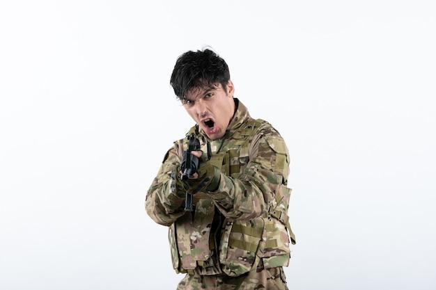 Vue de face du jeune soldat combattant avec un mur blanc de mitrailleuse