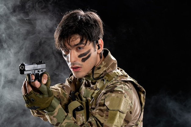 Vue de face du jeune soldat en tenue de camouflage avec pistolet sur mur noir