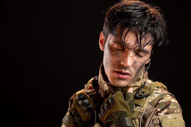 Vue de face du jeune soldat en uniforme sur un mur sombre