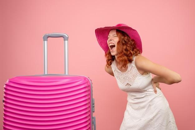 Vue de face du jeune touriste avec chapeau rose et sac sur mur rose