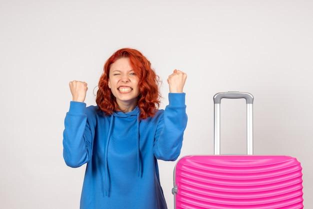 Vue de face du jeune touriste femelle avec sac rose sur mur blanc