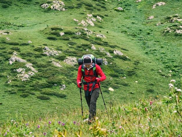 Vue de face du jeune touriste avec sac à dos et bâtons de randonnée marchant sur les collines verdoyantes