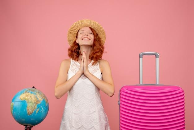 Vue de face du jeune touriste avec sac rose souriant et priant sur le mur rose