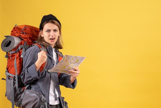 Vue de face du jeune voyageur confus avec sac à dos tenant la carte