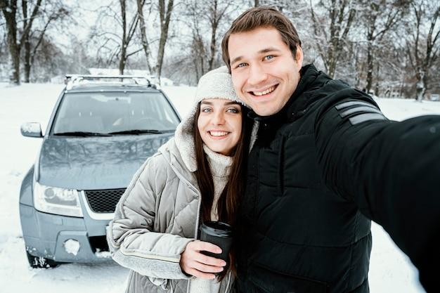 Vue de face du joli couple prenant selfie lors d'un road trip