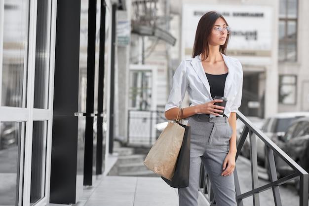 Vue de face du joli modèle posant debout près du magasin, transportant des sacs et du café.