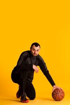 Vue de face du joueur de basket-ball posant dans un genou avec ballon et copie espace