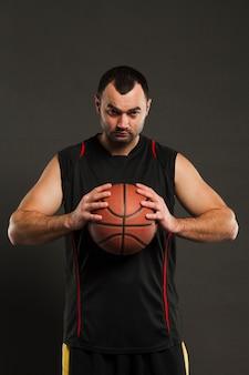 Vue de face du joueur de basket-ball posant et tenant le ballon près de la poitrine