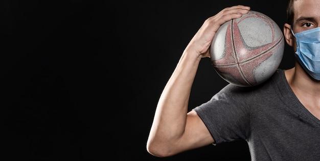Vue de face du joueur de rugby masculin avec masque médical et ballon