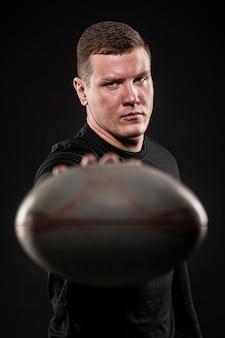 Vue de face du joueur de rugby masculin tenant ballon défocalisé