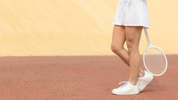 Vue de face du joueur de tennis bas des jambes avec une raquette