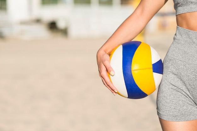 Vue de face du joueur de volley-ball féminin sur la plage tenant le ballon avec copie espace