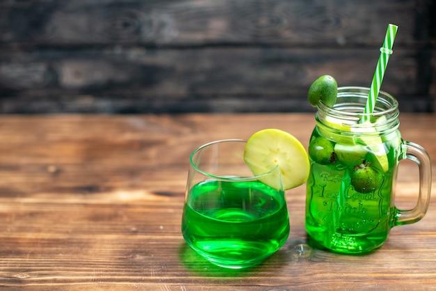 Vue de face du jus de feijoa frais à l'intérieur de la boîte et du verre sur le bar noir cocktail de fruits couleur boisson photo