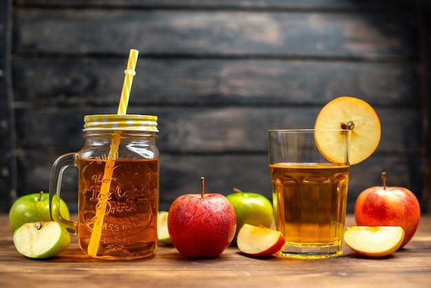 Vue de face du jus de pomme frais à l'intérieur de la boîte avec des pommes fraîches sur un bureau de couleur sombre boisson cocktail photo fruit