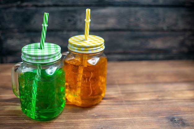 Vue de face du jus de pomme frais à l'intérieur des canettes sur la couleur de la barre de photo de boisson aux fruits noirs