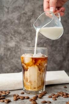 Vue de face du lait versé dans du café glacé
