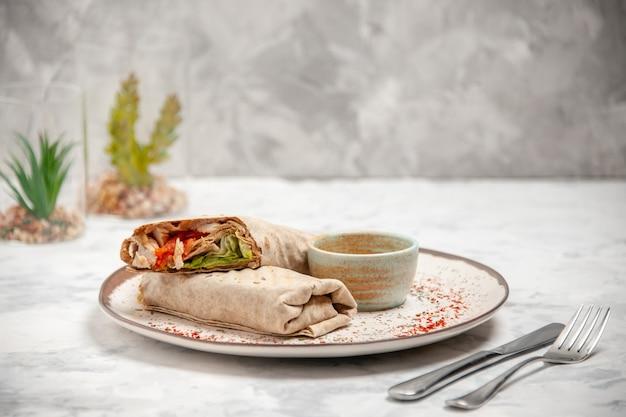 Vue de face du lavash wrap et du yaourt dans un petit bol sur une assiette et des couverts posés sur une surface blanche tachée