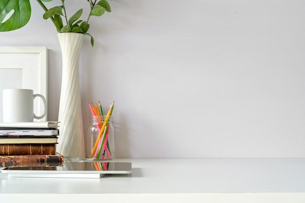 Vue de face du lieu de travail, espace copie, tablette, affiche de la maquette sur la table blanche de loft.