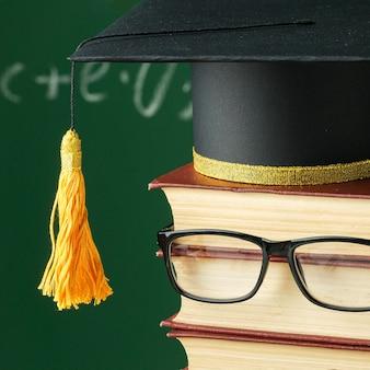 Vue de face du livre empilé avec des lunettes et une casquette académique