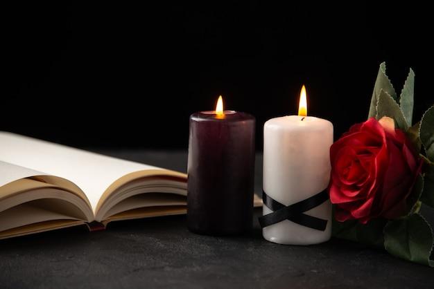 Vue de face du livre ouvert avec des bougies et rose sur fond noir