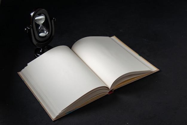 Vue de face du livre ouvert avec sablier sur fond noir