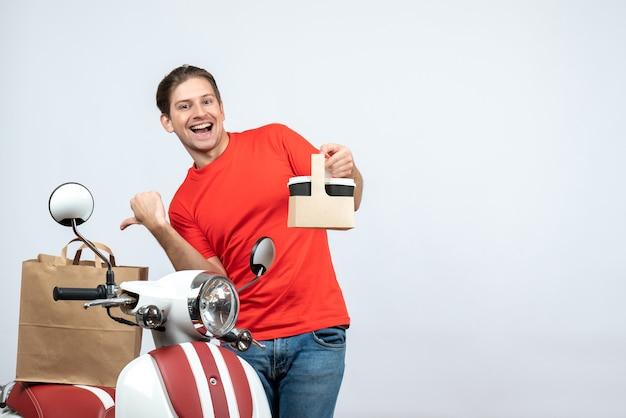 Vue de face du livreur émotionnel drôle en uniforme rouge debout près de l'ordre de pointage du scooter sur fond blanc