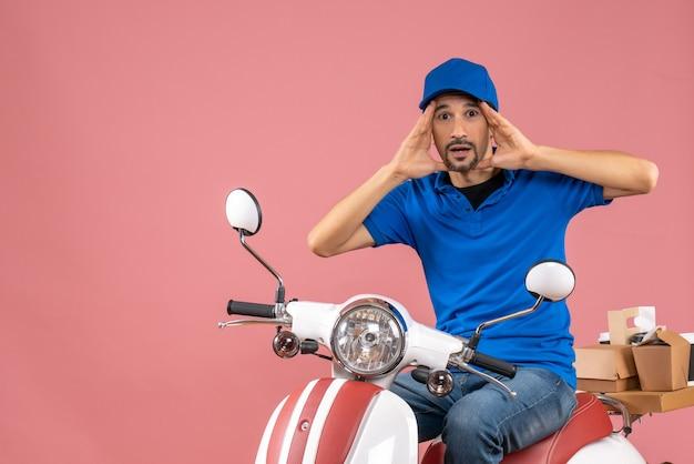 Vue de face du livreur surpris portant un chapeau assis sur un scooter sur fond de pêche pastel